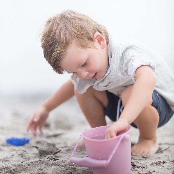 Scrunch - Flexibel Emmertje - pastel roze op het strand met jongetje
